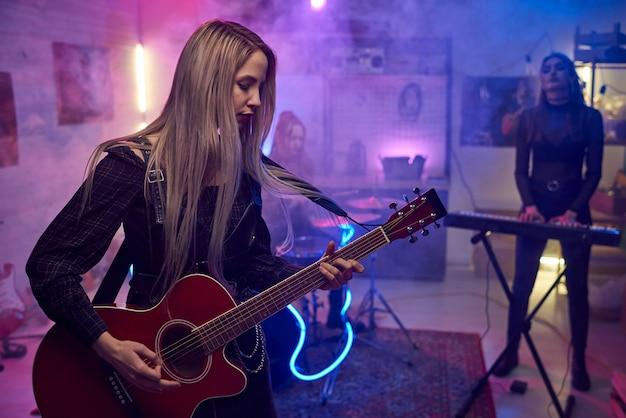 Młoda kobieta gra na gitarze ze swoją grupą muzyczną podczas występu w klubie nocnym