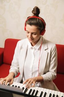 Młoda kobieta gra na syntezatorze w domu
