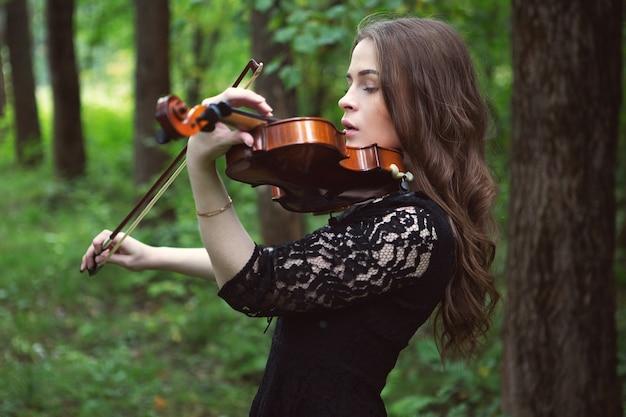 Młoda kobieta gra romantyczny utwór na skrzypcach w parku
