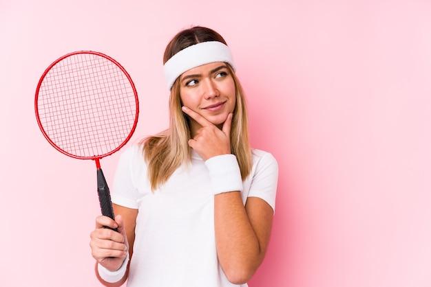 Młoda kobieta gra w badmintona na białym tle patrząc z ukosa z wyrazem wątpliwości i sceptycyzmu.