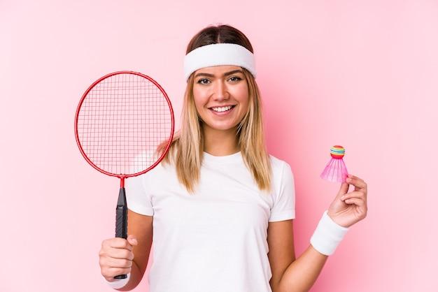 Młoda kobieta gra w badmintona na białym tle szczęśliwa, uśmiechnięta i wesoła.