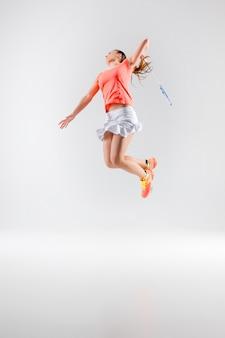 Młoda kobieta gra w badmintona na białym tle