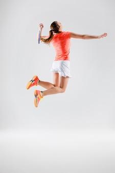 Młoda kobieta gra w badmintona na białym
