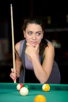 Młoda kobieta gra w bilard w ciemnym klubie bilardowym
