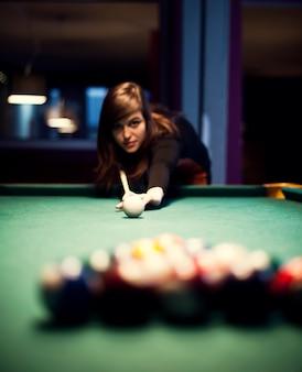 Młoda kobieta gra w bilard
