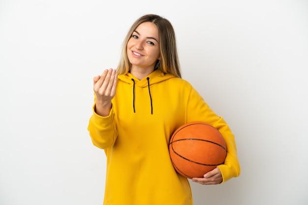 Młoda kobieta gra w koszykówkę na białym tle i robi nadchodzący gest
