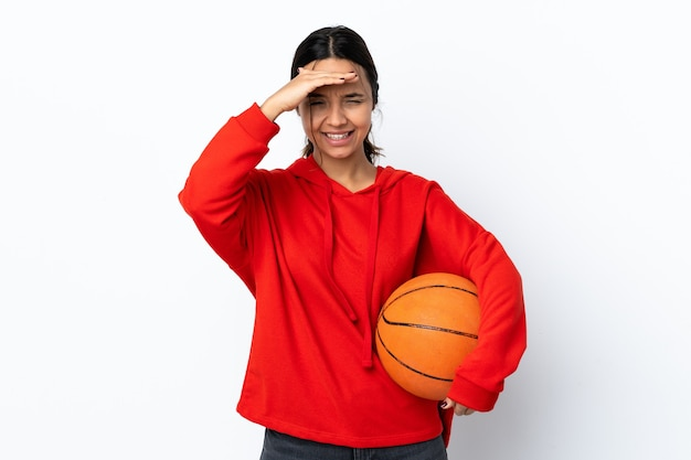 Młoda kobieta gra w koszykówkę na białym tle patrząc daleko ręką, aby coś spojrzeć