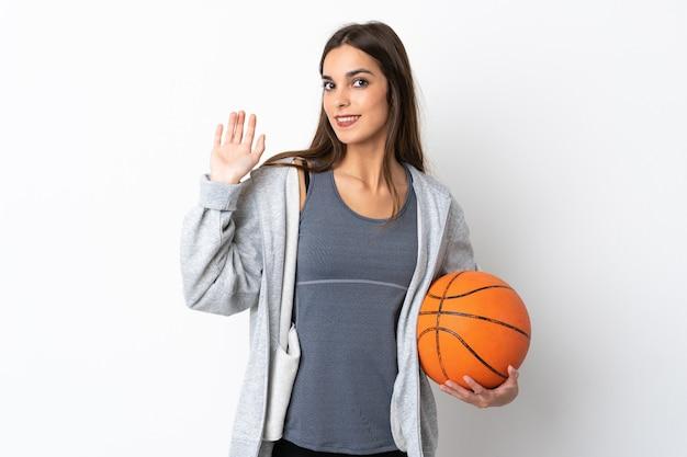 Młoda kobieta gra w koszykówkę na białym tle salutowania ręką z happy wypowiedzi