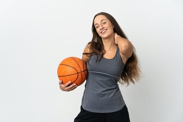 Młoda kobieta gra w koszykówkę na białym tle, śmiejąc się