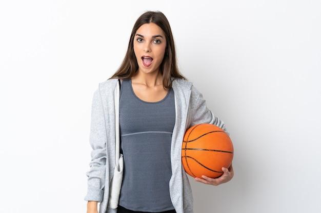 Młoda kobieta gra w koszykówkę na białym tle z zaskoczenia wyraz twarzy