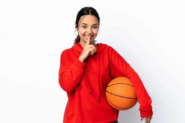 Młoda kobieta gra w koszykówkę na pojedyncze białe ściany przedstawiające znak gestu ciszy wkładając palec do ust