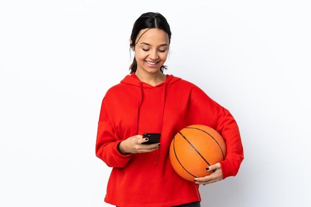 Młoda kobieta gra w koszykówkę na pojedyncze białe ściany, wysyłając wiadomość z telefonu komórkowego
