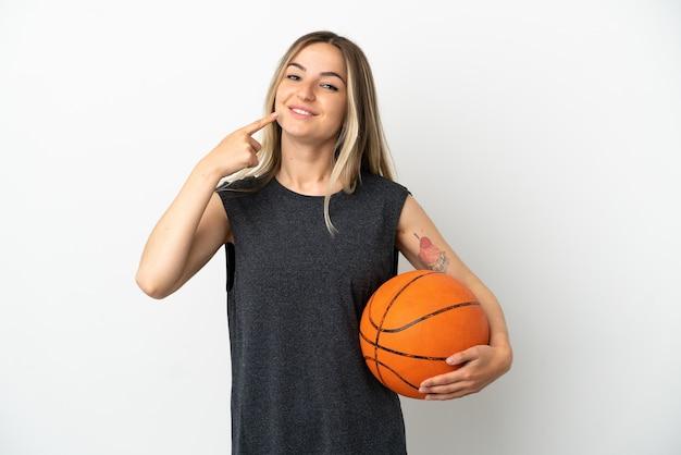 Młoda kobieta gra w koszykówkę nad odosobnioną białą ścianą, dając gest kciuka w górę
