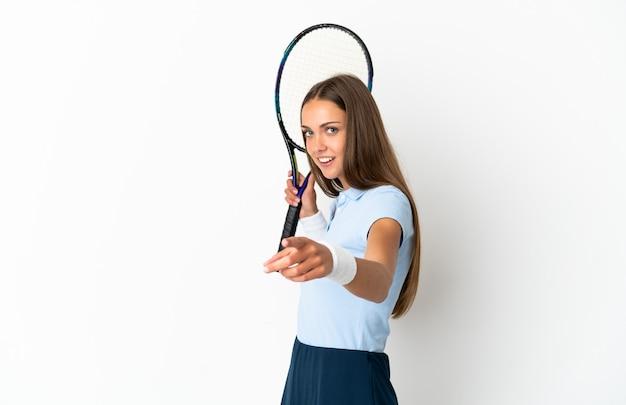 Młoda kobieta gra w tenisa na odosobnionym białym tle