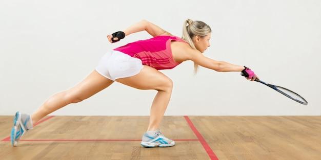 Młoda kobieta gra w tenisa w pomieszczeniu