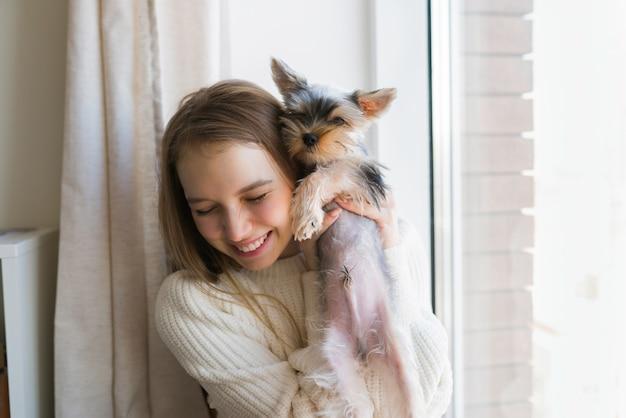 Młoda kobieta gra z psem na weekend w domu. szczęśliwy szczeniak yorkshire terrier