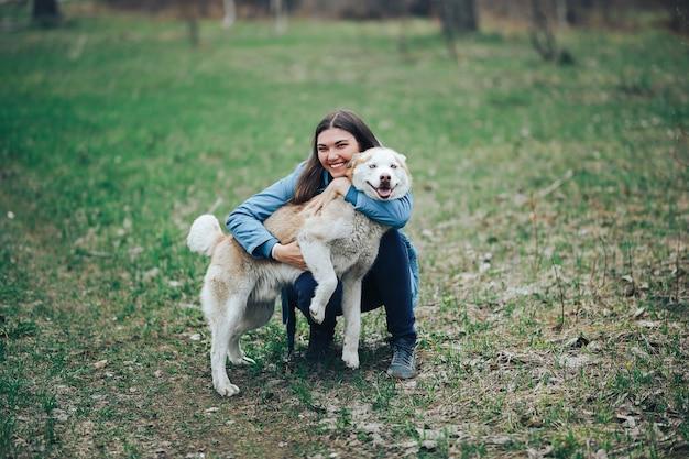 Młoda kobieta grać z psem husky na spacer w lesie wiosną. śmiejąc się bawiąc, szczęśliwy ze zwierzakiem