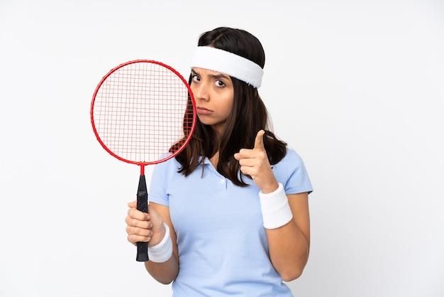 Młoda kobieta gracz badmintona na białym tle sfrustrowany i wskazując na przód
