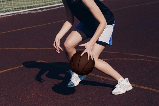 Młoda kobieta gracz koszykówki bawić się uliczną piłkę