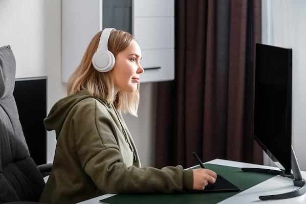 Młoda kobieta grafik freelancer zajęty pracą zdalnie z domu przy użyciu komputera pc i tabletu graficznego we wnętrzu salonu. dorywcza dziewczyna nastolatka w losowaniach, studiująca animację i sztuki wizualne.