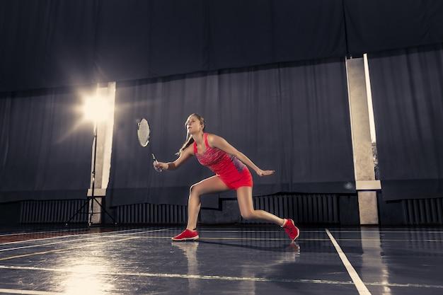 Młoda kobieta, grając w badmintona na siłowni
