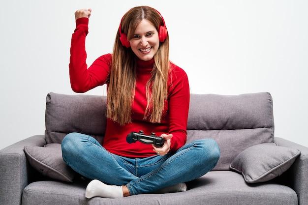 Młoda kobieta grając w gry wideo w domu