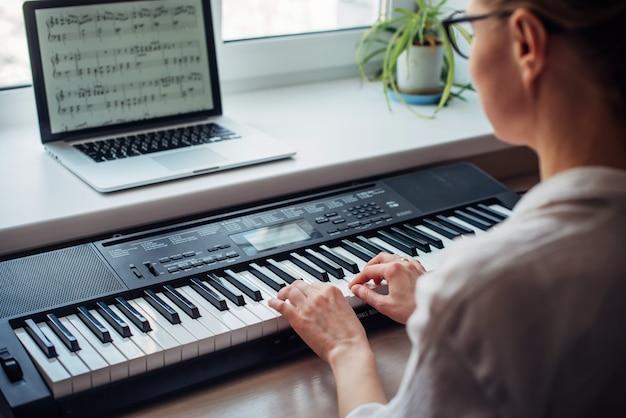 Młoda kobieta grająca na syntezatorze, czytająca nuty na laptopie, samodzielna nauka gry na pianinie