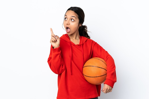 Młoda kobieta grająca w koszykówkę na białym tle, myśląca o pomyśle wskazującym palec w górę
