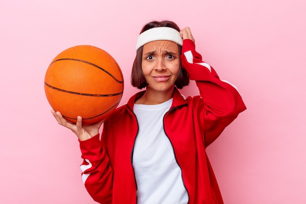 Młoda kobieta grająca w koszykówkę na białym tle na różowej ścianie, będąc w szoku, przypomniała sobie ważne spotkanie