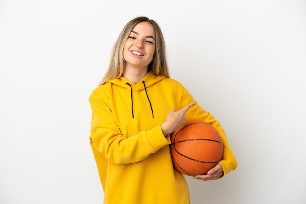 Młoda kobieta grająca w koszykówkę na odosobnionym białym tle i wskazująca na bok
