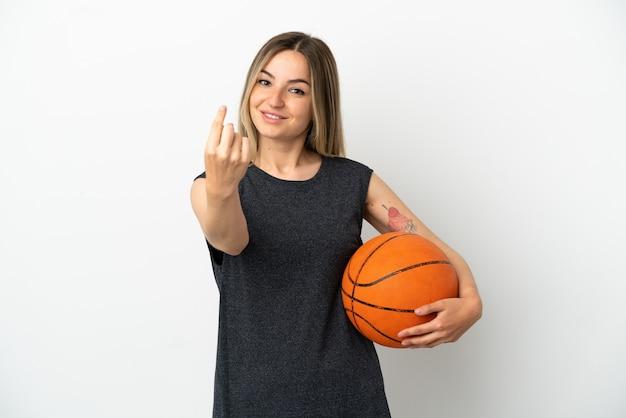 Młoda kobieta grająca w koszykówkę nad odosobnioną białą ścianą robi nadchodzący gest