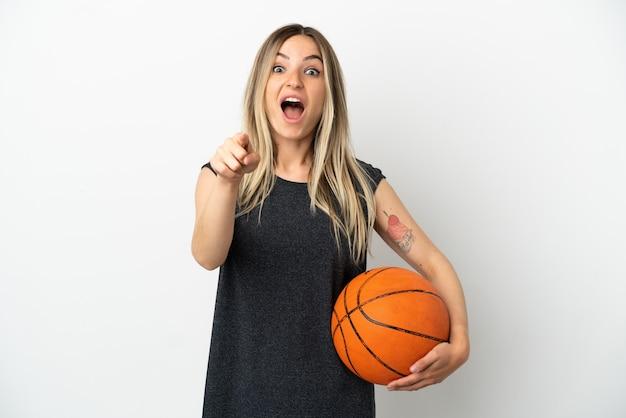 Młoda kobieta grająca w koszykówkę nad odosobnioną białą ścianą zaskoczona i wskazująca przód