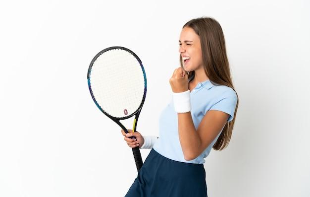 Młoda kobieta grająca w tenisa na białym tle i świętująca zwycięstwo