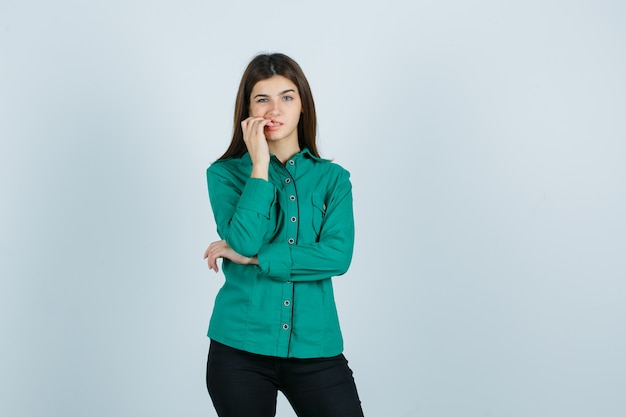 Młoda kobieta gryzie paznokcie w zielonej koszuli, spodniach i wygląda na zmartwioną. przedni widok.
