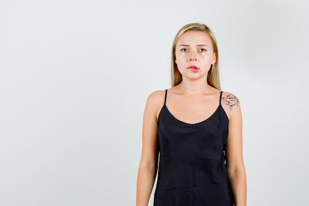 Młoda kobieta gryzie usta w czarną sukienkę i wygląda poważnie.