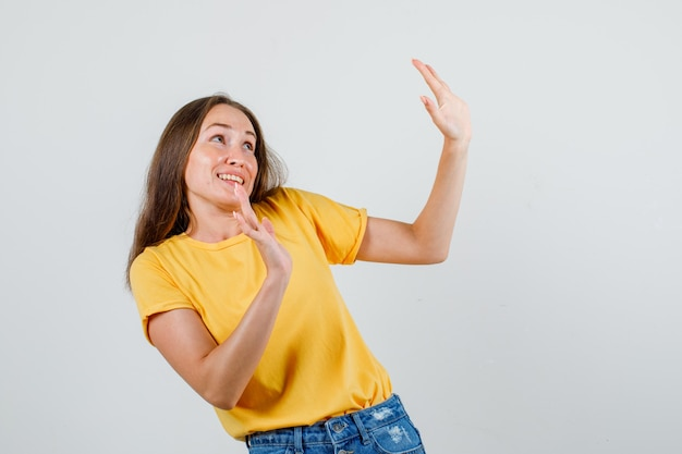 Młoda kobieta grzecznie pokazująca odmowę w t-shircie, szortach i wyglądająca na przestraszoną