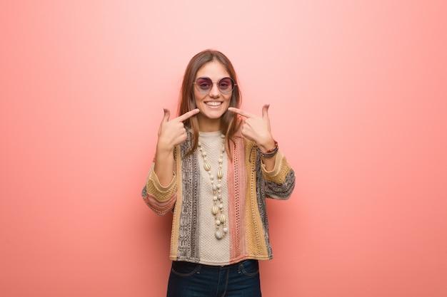 Młoda kobieta hipis na różowym tle uśmiecha się, wskazując usta