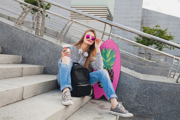 Młoda kobieta hipster na ulicy z równowagi na sobie sweter i dżinsy