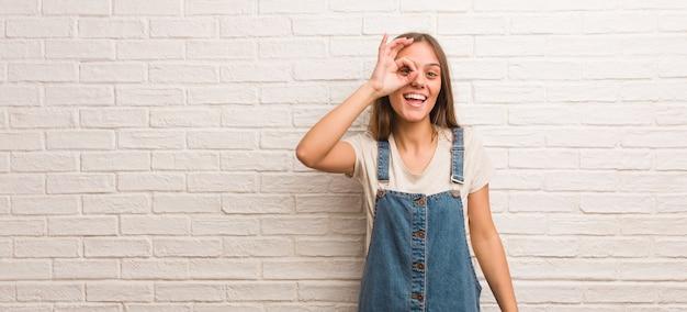 Młoda kobieta hipster pewnie robi ok gest na oko