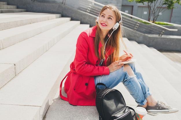 Młoda kobieta hipster w różowy płaszcz, dżinsy, siedząc na ulicy z plecakiem i kawą, słuchanie muzyki na słuchawkach
