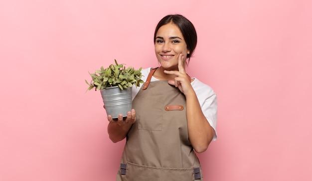 Młoda kobieta hispanic uśmiecha się radośnie i marzy lub wątpi, patrząc w bok