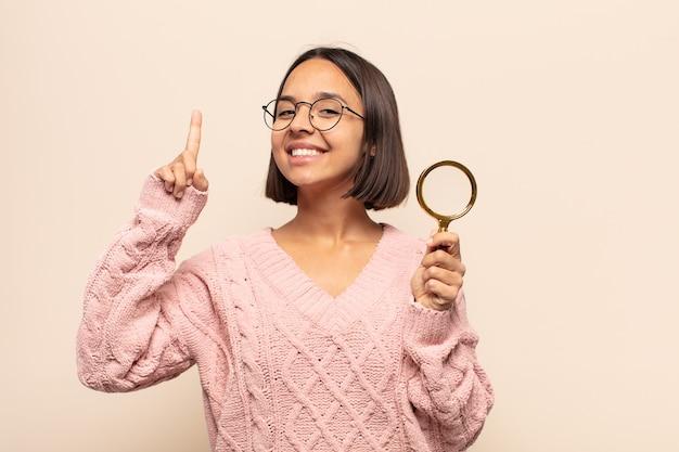 Młoda kobieta hispanic uśmiecha się radośnie i szczęśliwie, wskazując w górę jedną ręką, aby skopiować miejsce