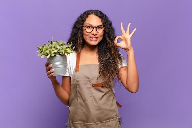 Młoda kobieta hiszpanin czuje się szczęśliwa, zrelaksowana i usatysfakcjonowana, okazując aprobatę gestem ok, uśmiechając się. koncepcja ogrodnika
