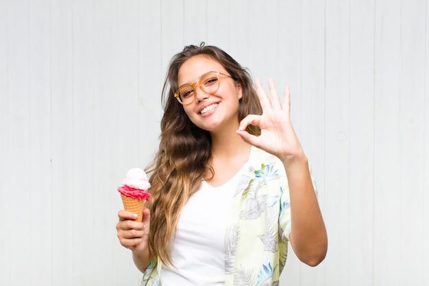 Młoda kobieta hiszpanin czuje się szczęśliwa, zrelaksowana i usatysfakcjonowana, okazując aprobatę gestem ok, uśmiechając się