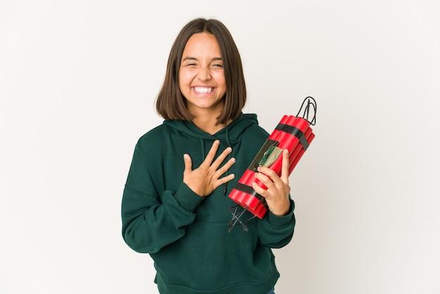 Młoda kobieta hiszpanin gospodarstwa dynamitu śmieje się głośno, trzymając rękę na klatce piersiowej.