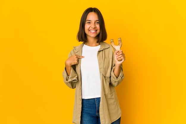 Młoda kobieta hiszpanin gospodarstwa osoba proca, wskazując ręką na przestrzeni kopii koszuli, dumny i pewny siebie