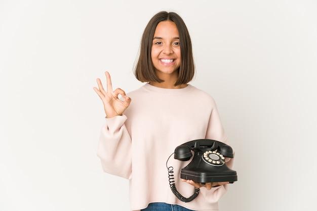 Młoda kobieta hiszpanin gospodarstwa rocznika telefon na białym tle wesoły i pewny siebie, pokazując ok gest.