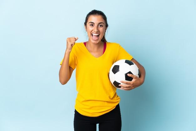 Młoda kobieta hiszpanin grający na pozycji napastnika na izolowanych na niebieskim tle świętuje zwycięstwo w pozycji zwycięzcy