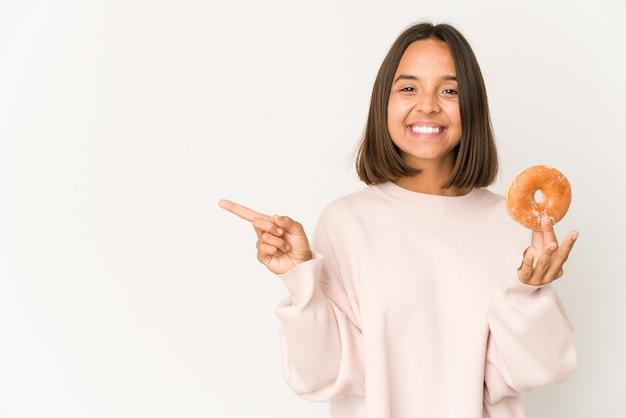 Młoda kobieta hiszpanin jedzenie pączka, uśmiechając się i wskazując na bok, pokazując coś w pustym miejscu