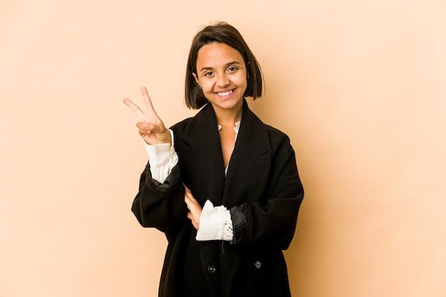 Młoda kobieta hiszpanin na białym tle pokazuje numer dwa palcami.